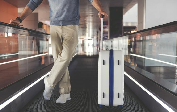 Pasażer na lotnisku z walizką w wadze 20 kg